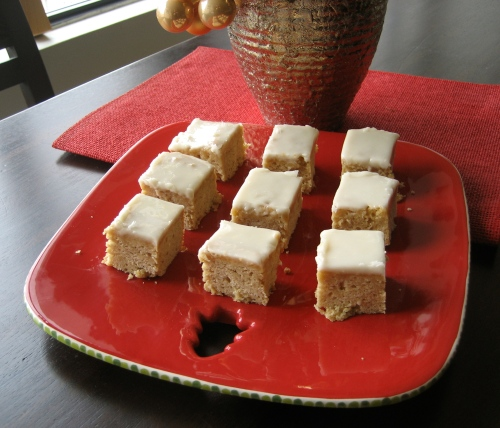Nine maple squares on a red christmas plate with a gold plant pot in the background